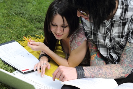 Couple of young students studying outdoors with laptop and books Stock Photo - 12757371