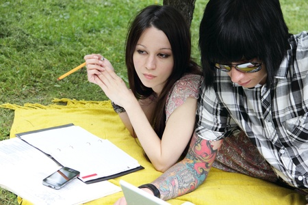 Couple of young students studying outdoors with laptop and books photo