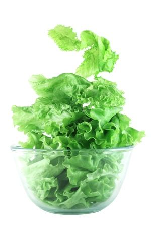 Light lettuce salad in transparent bowl isolated on white lightness concept