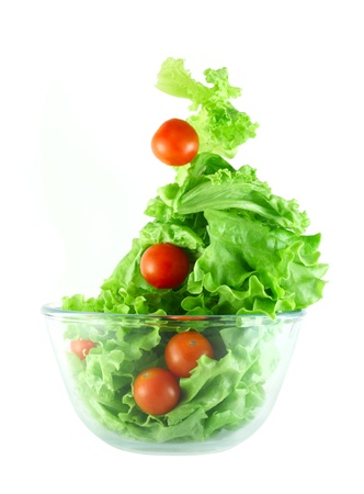 Light lettuce and cherry tomatoes salad in transparent bowl isolated on white lightness concept