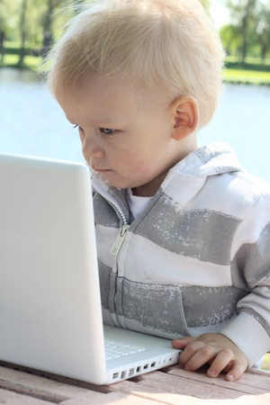 small child working with laptop outdoor photo