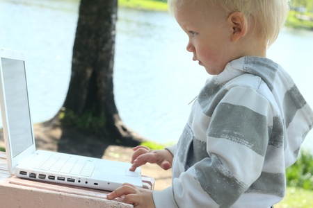 small child working with laptop outdoor Stock Photo - 12908539