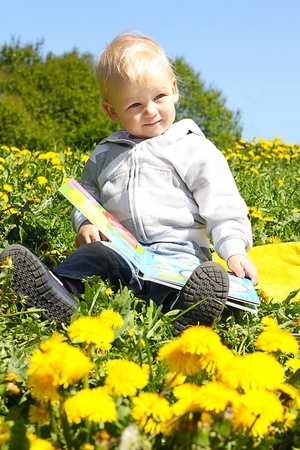 small child reading a book in flower field Stock Photo - 12908556