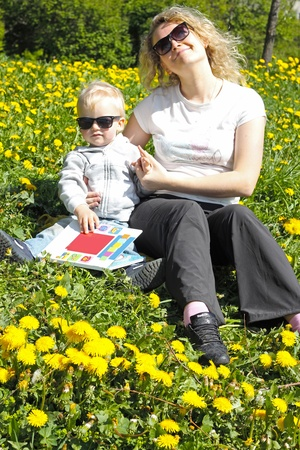 Mother and child on flower field reading a book photo