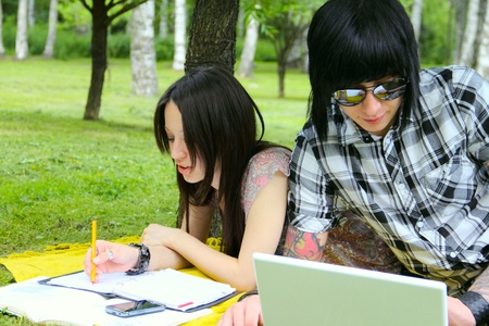 Couple of students studying outdoor with laptop photo