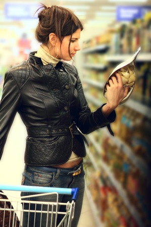 Young woman with shopping cart in supermarket choosing pasta Stock Photo - 13100613