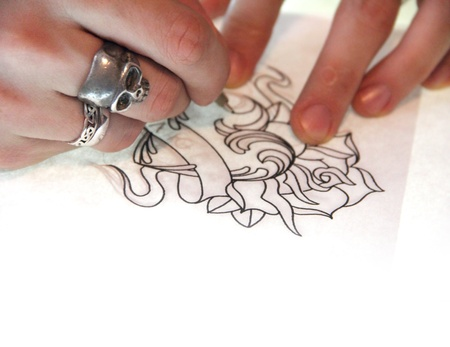 Artist drawing sketch of tattoo on white paper photo