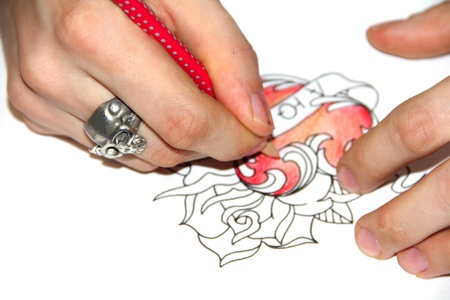 Artist drawing sketch of tattoo with red pencil photo