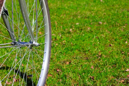 Bicycle wheel on first spring grass background