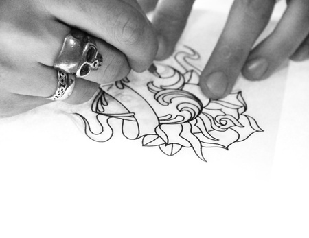 Artist drawing sketch of tattoo on white paper bw photo