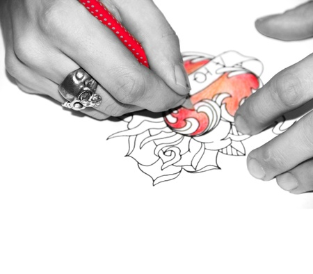 Artist drawing sketch of tattoo with red pencil