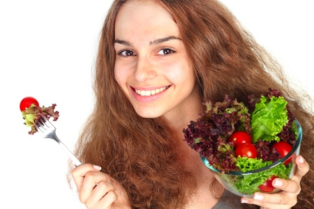 Young woman eating vegetable salad isolated on white Stock Photo - 13962796