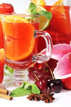 Refreshment beverage in glass with fruits and spice close-up photo