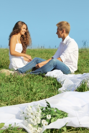Young man and woman sitting on green field and talking Stock Photo - 14779632