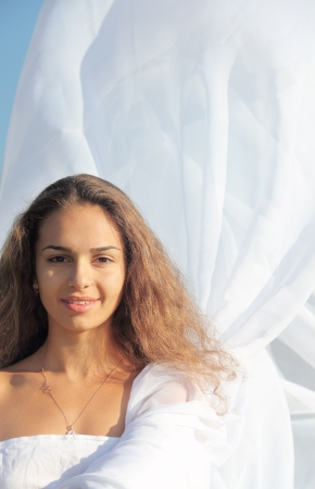 Portrait of a young woman wearing white dress outdoors photo