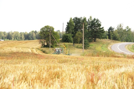 Tractor with hay at yellow wheat field in summer day  photo