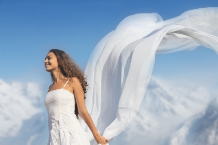 Young fresh woman with flying fabric on top of the mountains photo