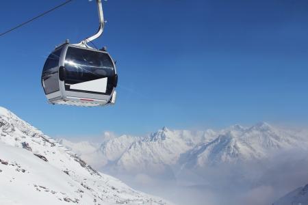 山と青空の下で冬のアルプスのパノラマ ビューでチェアリフト 写真素材