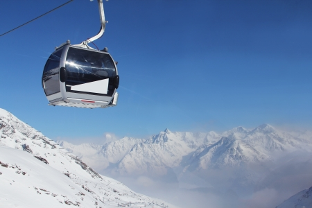 ropeway: Chairlift in mountains and panoramic view on winter alps under blue sky Stock Photo