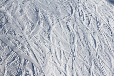 Ski traces on snow in mountains at sunny day photo