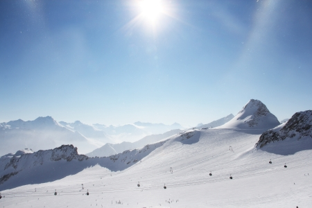 Mountain peaks of winter alps under blue sky photo