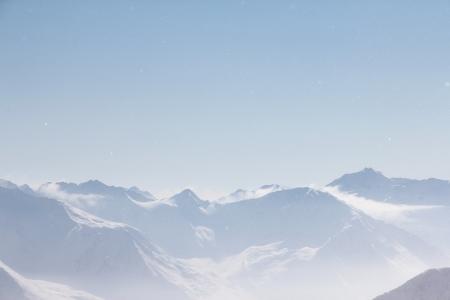 Mountain peaks of winter alps under blue sky photo