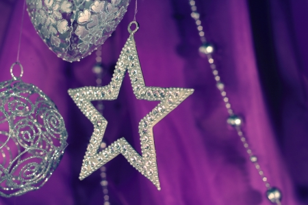 Silver christmas decoration on purple fabric background photo