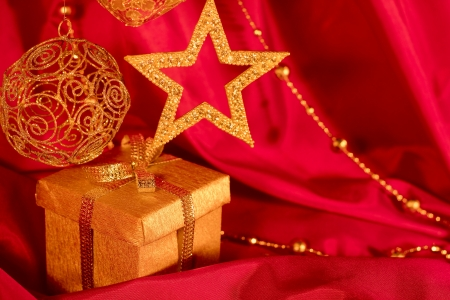Golden christmas decoration and gift on red fabric background photo