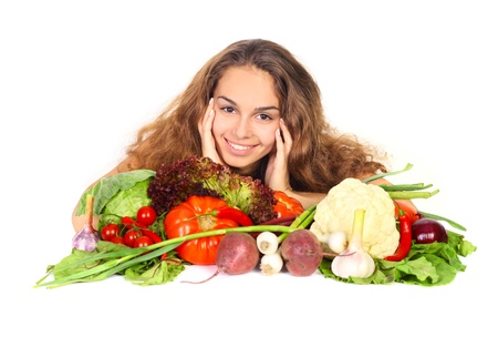 Beautiful young woman with a pile of vegetables isolated on white photo