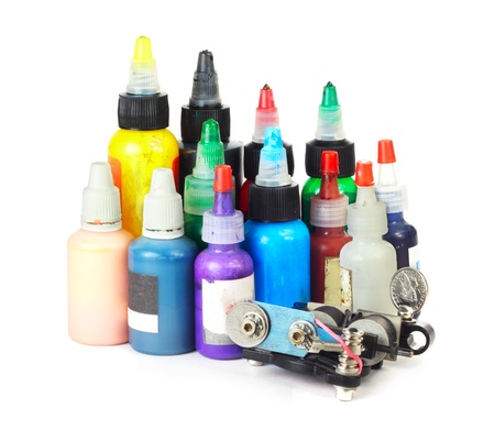 Tattoo machine with many color ink bottles isolated white background photo