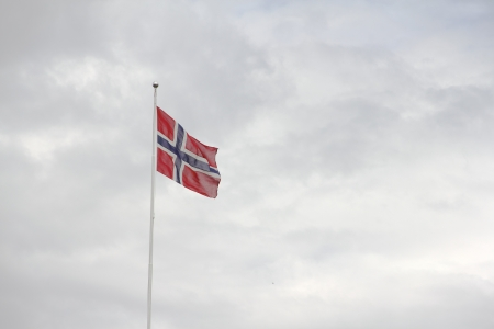 Norway Flag on cloudy sky background photo