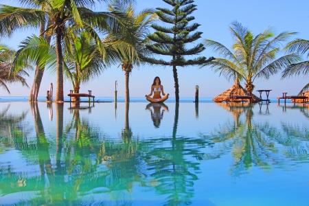熱帯のビーチでのスイミング プールのそばの美しい女性