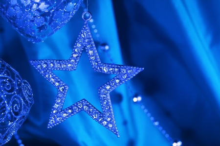 Silver christmas decoration on blue fabric background photo