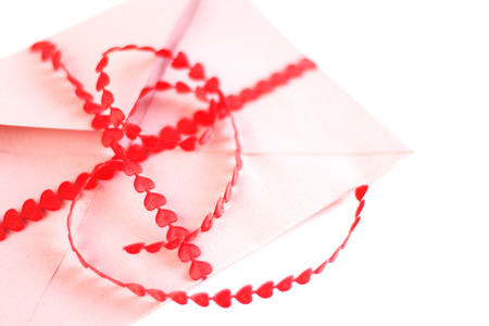 Envelope with red hearts ribbon isolated on white background photo