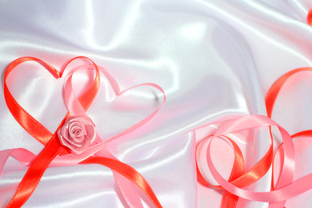 Red and pink satin glossy ribbon hearts and roses over white silk background photo