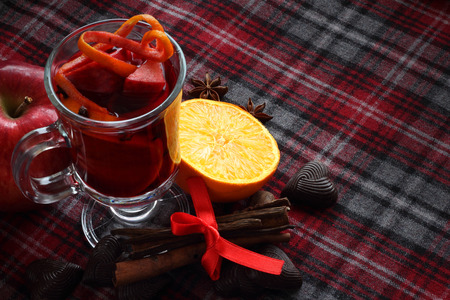 Hot red mulled wine with fruits and cinnamon on checkered tablecloth photo