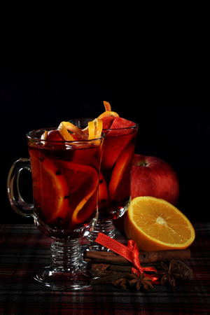 Hot red mulled wine with fruits and cinnamon on checkered tablecloth Stock Photo