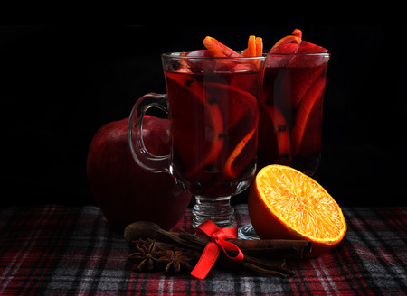 punch: Hot red mulled wine with fruits and cinnamon on checkered tablecloth Stock Photo
