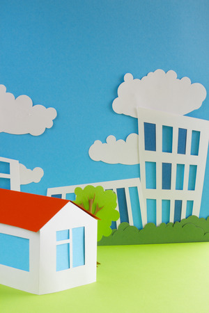 Paper cottage over city background real estate concept photo