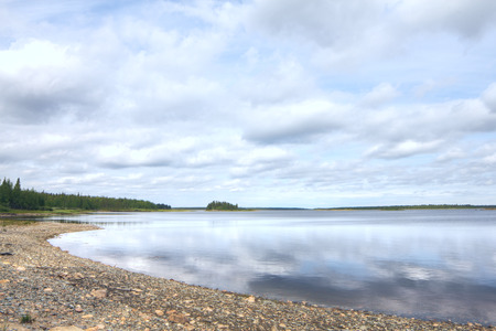 Finnish landscape with a forest lake with stones photo