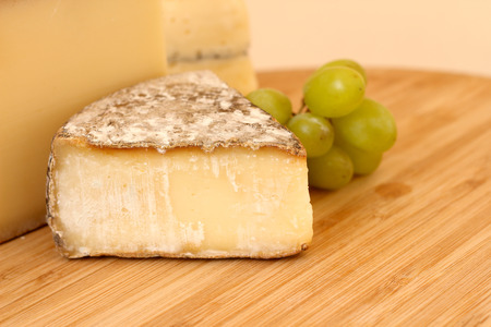Cheese and green grapes on wooden board photo