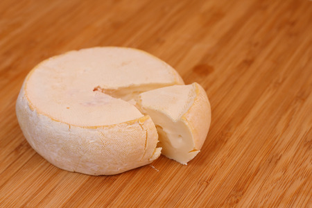 Camembert cheese on wooden board close-up photo