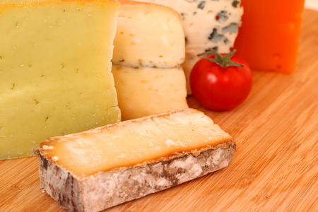 Various types of french cheese on wooden board close-up photo