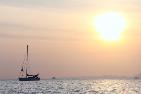 Sailing yacht in open sea on beautiful sunset sky  photo