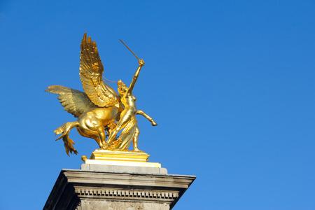parisian scene: Alexander III bridge sculpture in Paris over sky background
