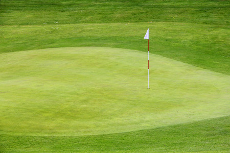 Golf flag on the green grass field close up photo