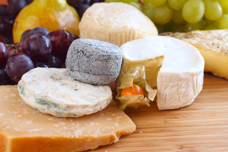 French cheese composition on wooden plank table photo
