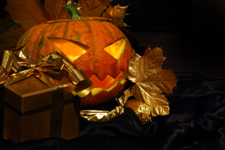 Halloween pumpkin with autumn leafs and gift on black