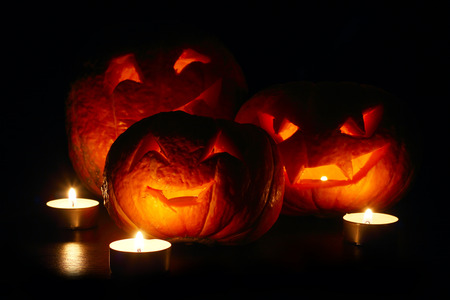 Illuminated cute halloween pumpkins and candles isolated on black