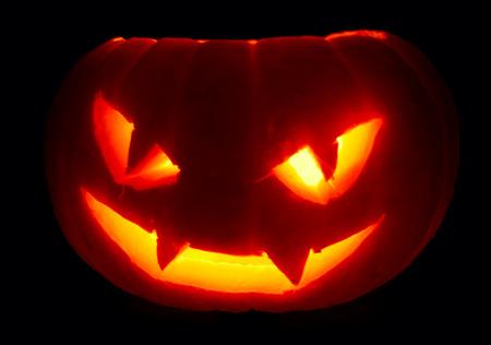 Illuminated cute halloween pumpkin isolated on black background photo